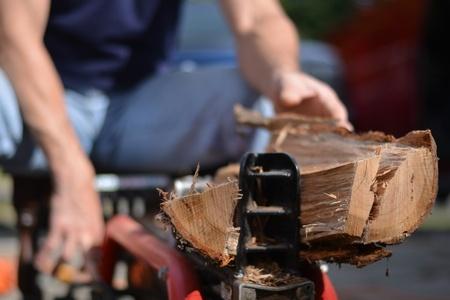 Mies pilkkoo puita halkomakoneella.